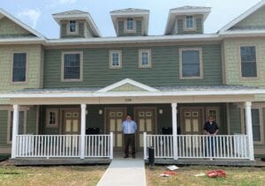 Two men stand in front of a house.