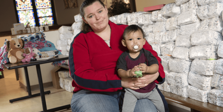 Mother holds baby next to a pile of diapers