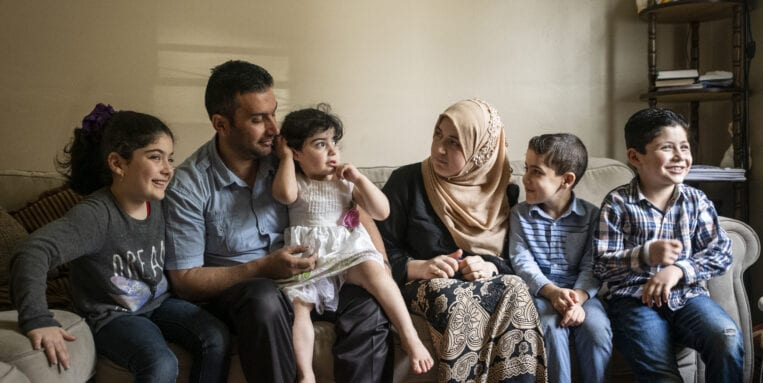 The Alhariris, a New American Family, sit together in their Syracuse home