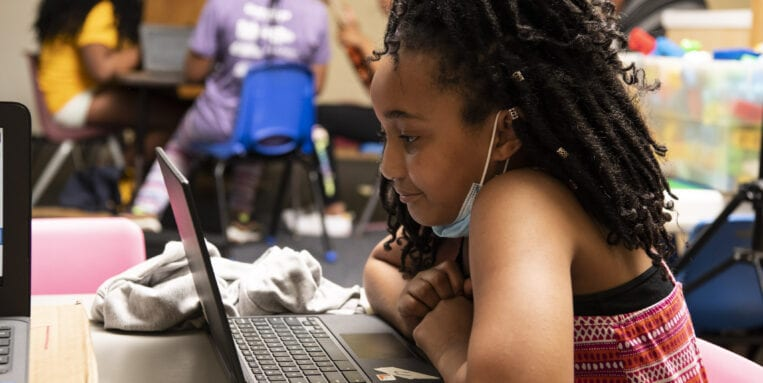 Young girl works on a laptop in the classroom